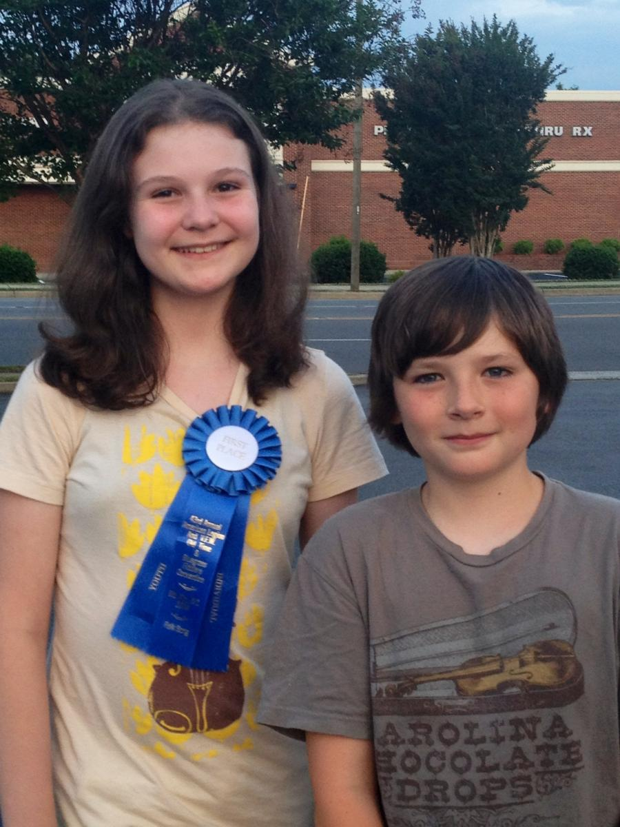In 2014, Eliza Meyer earned 1st place at Mt. Airy Fiddlers' Convention in the Youth Folksong competition. She was backed on banjo by Liam Purcell, also pictured.