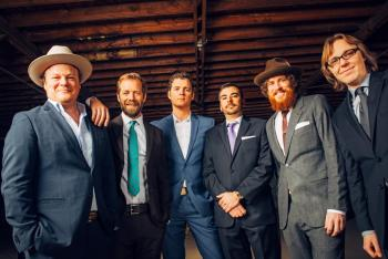 The six members of the Steep Canyon Rangers standing side by side in blue or gray suits in this promotional photo - 4 are wearing ties, 2 are not; 2 are wearing hats, 4 are not. On Friday, Nov. 11, the Steep Canyon Rangers will lead a workshop at 3 p.m., and they will perform a ticketed concert at 8 p.m. at UNC's Memorial Hall.