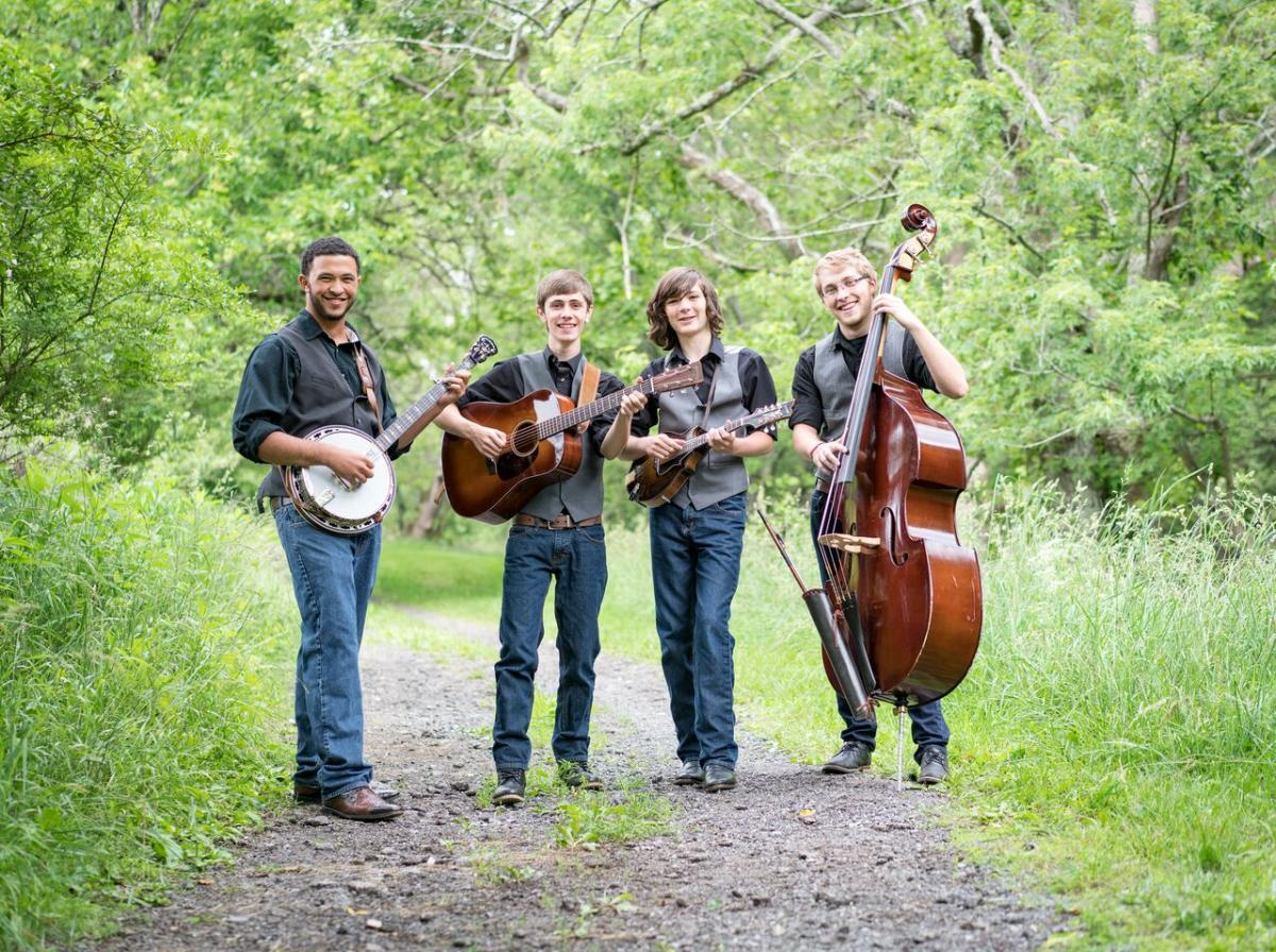 The four members of Cane Mill Road standing outside on a gravel road with grass, trees, and bushes visible behind them and beside the road. All four are smiling. From left to right: Trajan Wellington with banjo; Casey Lewis with guitar; Liam Purcell with mandolin; and Eliot Smith with bass. All four wear blue jeans, dark boots, and dark button down collared shirts with the sleeves rolled up to their elbows; Casey, Liam, and Eliot each wear a gray vest.