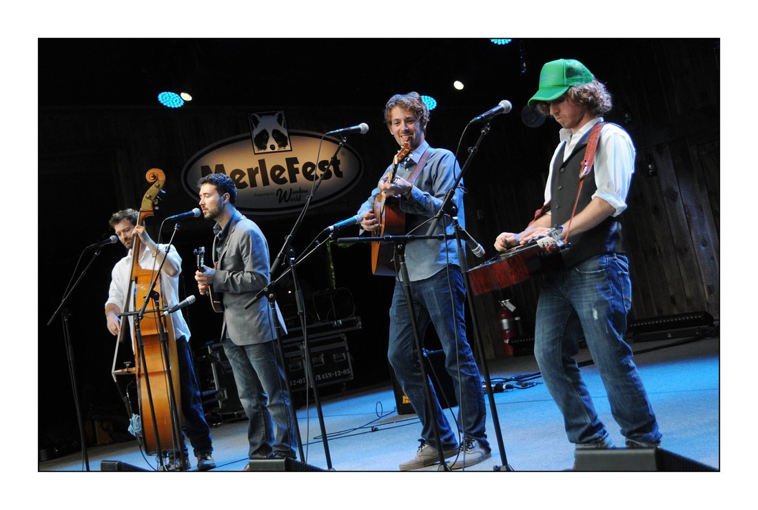 Promotional photo of Fireside Collective on stage at Merlefest with their respective instruments: Carson White (bass), Jesse Iaquinto (mandolin), Joe Cicero (guitar), Tommy Maher (dobro).