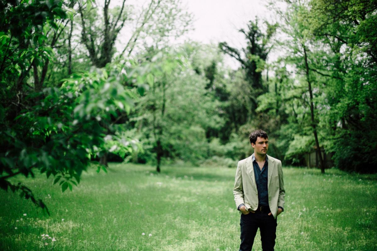 Promotional photo: Jordan Tice, wearing dark slacks and a dark shirt, and a light jacket, standing outside in a field with trees in the background.