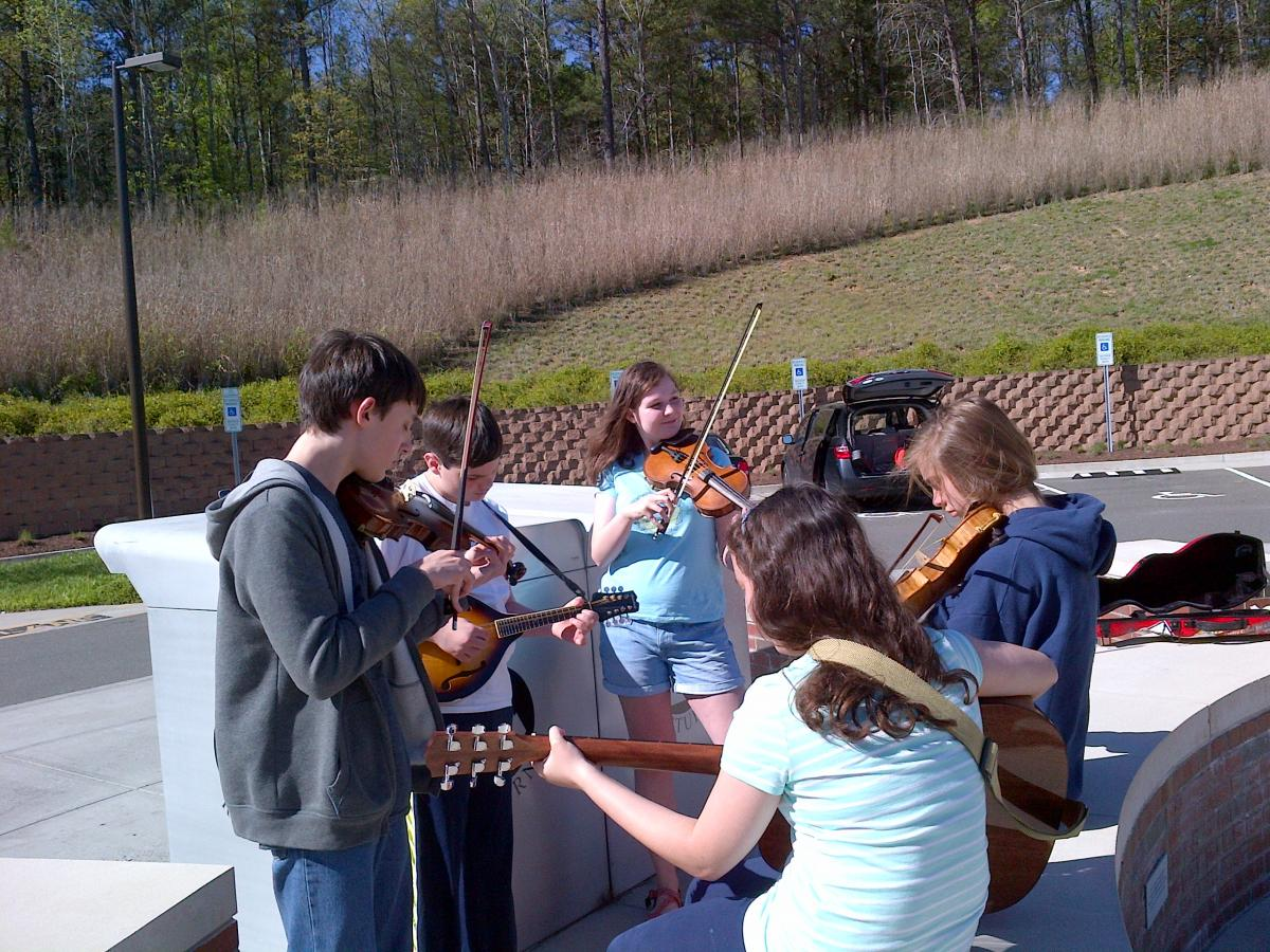 Members of PineCone Youth Council - 3 female, 2 male - playing their instruments together outside the Chapel Hill Library after a jam.