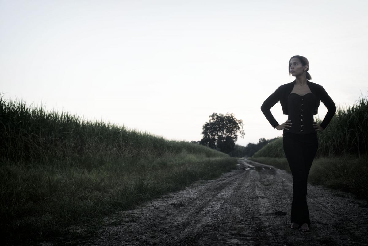 Rhiannon Giddens stands with her hands on her hips, looking off into the distance over her right shoulder. She is wearing dark pants, a dark fitted top, and a short dark jacket with long sleeves. She is on the side of a dirt road with tall grass growing in fields on either side of it.