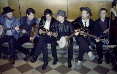 Members of Old Crow Medicine Show seated on a bench. Each man holds an instrument, from left to right: banjo, fiddle, mandolin, banjo, guitar, bass. All have light skin; the guitar player has shoulder length blonde hair and wears a hat; the others have dark hair. Both banjo players also wear hats.