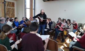 Singers gathered together at the 2016 Sacred Harp Convention; men and women of various ages sit together around a square holding songbooks, and a man stands in the middle of the square leading the song.