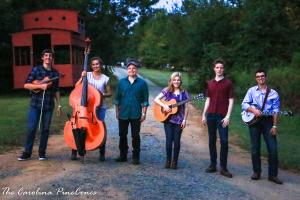 The Carolina PineCones stand side by side outdoors on a dirt road, with grass visible to either side of them and trees and a building visible in the background. Sam Stage (holding fiddle), Carter Ramquist (standing beside her bass), Jef Walter, Jessie Lang (with guitar), Aidan Buehler, Anthony DeCesaris (with banjo).