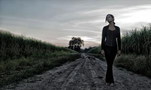 Rhiannon Giddens, wearing all black (slacks, top, and jacket) standing alone on a dirt road with a cloudy sky above and behind her and tall grasses on either side; a tree is also visible in the distance.