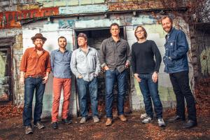 Promotional photo of Steep Canyon Rangers - Band members are casually dressed in jeans and long-sleeved shirts; 3 have facial hair, 2 are wearing hats, and one wears glasses. They are outside a small brick building (bricks mostly painted white, but some graffiti is visible as well), and there is deep brown, almost red dirt/mulch covering the ground.
