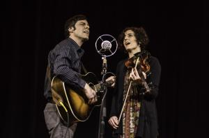 Promotional photo of Zoe & Cloyd: John Cloyd Miller with guitar and Natalya Zoe Weinstein on fiddle, sharing an old-style microphone.