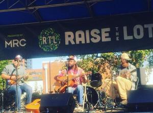 Sitting in folding chairs on an outdoor stage, from left to right: Kevin Burnet plays mandolin, Dwight Hawkins plays guitar, and Andrew Berger-Gross