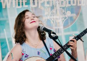 Eliza Meyer, a young woman with shoulder-length brown hair, plays a banjo seated in front of a microphone. Her head is tilted up and her eyes are closed; a Wide Open Bluegrass banner is partially visible in the background.