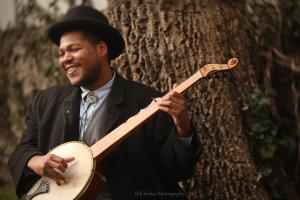 "Jerron ""Blind Boy"" Paxton playing banjo beside a tree. He is wearing a hat, a jacket and button-down shirt, and he has a bright smile."