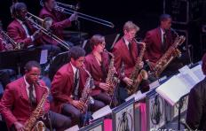 African American and Caucasian students, male and female, all in matching red coats and dark slacks (and the men all in white shirts with collars and neckties). Front row musicians play saxophones; back row musicians play trombones.
