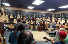 Men and women of varying ages sit in a large circle on chairs or stools; Jef Walter stands with his bass. Two walls of guitars are visible behind the musicians, and there's a worn rug in the middle of the circle that the participants are seated around. Photo credit: Spencer Mobley