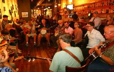 Musicians gathered in a circle at the Busy Bee Cafe - men and women of all ages sit in a circle playing guitars, banjos, fiddles, mandolins; the Busy Bee's Bar is along one wall, and the other brick wall has artwork hanging from it. Photo credit: Brainard Photo
