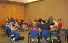 A group of youth students sitting in a circle in a room at Marbles Kids Museum playing fiddles and guitars; facilitator Jef Walter stands to play his guitar in the circle with the students; a few parents and others look on from outside the circle of young musicians.