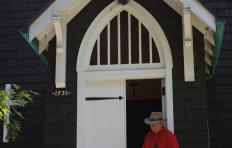 Joe Penland holds a fiddle and leans against the doorpost of a half-open door, right foot inside, left foot outside on the building's porch. He wears jeans, a short-sleeved shirt, and a western-style hat.