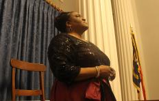 Mary D Williams stands in profile, looking up. Her hair is pulled back and she wears a dark sequined top with sleeves to her elbows, a shimmering skirt, dangling earrings, a necklace, bracelets on her right wrist, and wrings on both hands. In the background is a pair of floor-to-ceiling pillars and a North Carolina flag to Mary's left, and a curtain covers the wall behind her. She stands at a wooden desk with a wooden chair behind her.