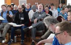 Men and women of various ages sit with books, some facing the camera, some in profile with their left shoulders toward the camera; singing together at the 2016 Sacred Harp Annual Convention in NC.