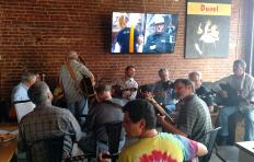 Musicians seated in an oval in the Speakeasy at Tyler's Taproom; one musician holding a guitar is standing up. Participants visible in this picture include guitar players, fiddler players, and banjo players. Background: a brick wall with a large TV hanging in the middle of it (the TV is on), and a Duvel poster hangs to the right of the TV; to the left side of the picture, there is a table with someone's plate of food and a partially consumed drink.