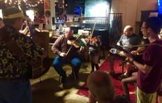 Some musicians gathered in a circle at the PineCone Bluegrass Jam at Imurj in June 2017. Fiddle players, guitar players, a dobro player, mandolin players, and upright bass player share a tune.