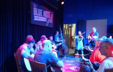 Musicians gathered in a circle at The Blue Note Grill; most seated, but three area standing: a man playing bass, a woman playing fiddle, and a man playing guitar. The Blue Note Grill banner is on the wall behind the musicians.