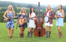 Promotional photo of Loose Strings Band - 5 young women stand outside in the grass with mountains and trees in the background. The women are all wearing different dresses and standing with their instruments: Lindsey Nale with mandolin; Channing Russell Combs with guitar; Grace Davis with bass; Ashley Nale with banjo; and Mary-Claire Hooper with fiddle.