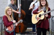 "The Lang Sisters Band standing on the front porch steps outside a door of a house with a grey brick facade, with the words ""THE LANG SISTERS BAND"" above the door frame in red. Front left: Jessie Lang - a young woman holding a mandolin; back left: Jef Walter stands holding up his upright bass on his left side; back right: Sam Stage holds his fiddle; front right: Chloe Lang holds her guitar. All 4 are smiling."