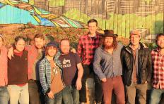 Songs from the Road Band: 9 men in a variety of outfits standing together in front of a colorful wall.