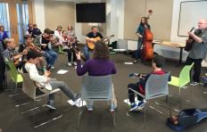 Students play guitars, mandolins, fiddles, banjo, and bass; most are seated around the room, though a young woman stands to play bass; facilitator Jef Walter stands and plays guitar.