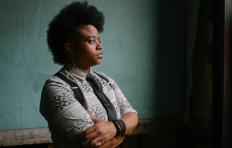 Amythyst Kiah stands in profile with her arms crossed in front of her, looking off into the distance. She wears suspenders, a tie, a collared shirt with sleeves down to her elbows, and a dark bracelet on her left wrist.