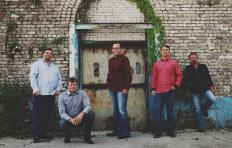 Promotional photo of The Boxcars - five men in various poses (standing, crouching, or leaning against the wall), outside an old brick building with a rusted door and some leaves growing up one side of the doorframe. The men all wear black shoes, blue jeans, and long-sleeved button down shirts. Three of the men have facial hair, two do not. All five have short hair; Adam Steffey, standing in the middle, is the only one wearing glasses.