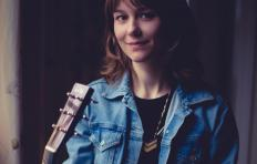 Molly Tuttle - a young woman with light skin, shoulder length brown hair, wearing a jean jacket and dark shirt, with a guitar neck to her right.