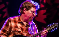 Tim O'Brien playing mandolin; he's wearing glasses and a plaid flannel shirt; he has light skin and sandy brown hair.