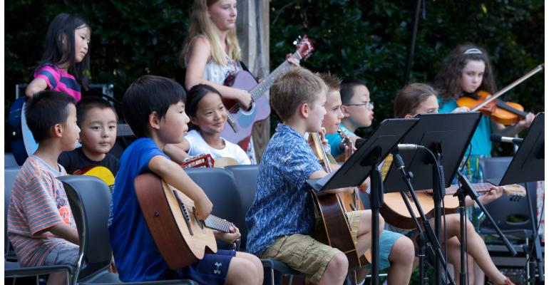 Students from PineCone's Youth Bluegrass Camps sit together on stage with their instruments during their culminating camp performance.