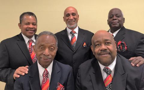The Gospel Jubilators - 5 African American men in white shirts, red ties, and black suits. Three stand in the back row, two in the front row. Two men in back have a hand on the shoulder of each of the men in front.