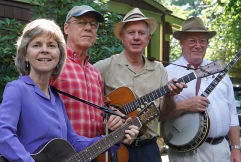Piney Woods Boys promotional photo, from left to right: Margaret Martin (with guitar), Matt Haney, Wayne Martin (with guitar), and Jim Collier (with banjo). Trees and a building are visible in the background.