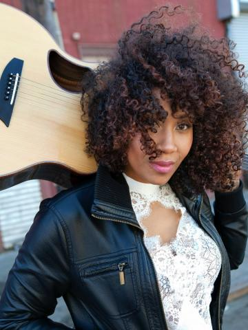 Rissi Palmer holds her guitar behind her head, partly visible over her right shoulder. Her dark, curly hair blows partly in front of her face; she is wearing a leather-textured jacket over a lacy white top.